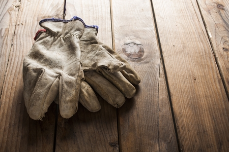 dirty clothes: Old working gloves over wooden table, construction tools