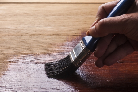 wood fence: and holding a brush applying  varnish paint  on a wooden surface