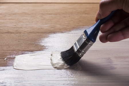 and holding a brush applying  varnish paint  on a wooden surface