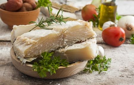 baccalà salato sul tavolo di legno con gli ingredienti