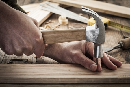 carpenter tools: woodworker hammer a nail Stock Photo