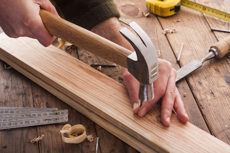 woodworker hammer a nail Stock Photo