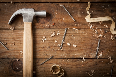 carpenter hammer, nail and shavings on wooden surface