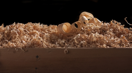 carpenter's sawdust: wood turning shavings on black background
