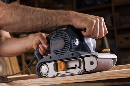 electrical materials: carpenter works with belt sander in carpentry