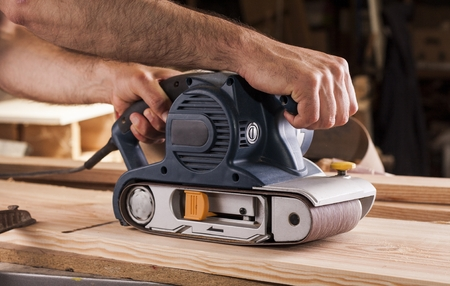 carpintero: carpintero trabaja con lijadora de banda en carpintería Foto de archivo