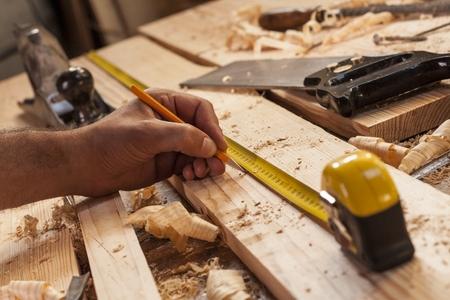 menuisier: charpentier de prendre la mesure d'une planche de bois