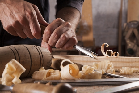 木工のワークベンチ上の手のガウジで彫る職人の手