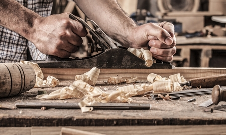 carpenter working with plane on wooden background Фото со стока - 64499714