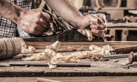 Carpintero que trabaja con el plano sobre fondo de madera Foto de archivo - 64499714