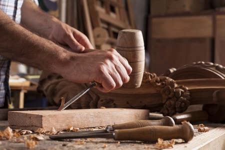 Hands of craftsman carve  with a gouge in the hands on the workbench in carpentry Stockfoto