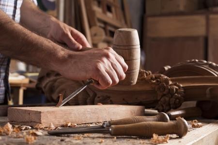 tallado en madera: Las manos del artesano tallar con una gubia en las manos sobre la mesa de trabajo en la carpintería