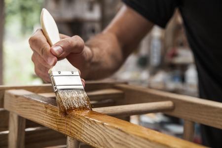 muebles de madera: mano que sostiene un cepillo de aplicación de pintura barniz sobre un mueble de madera