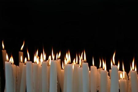 luz de velas: Llamas de la vela blanca sobre un fondo negro  Foto de archivo