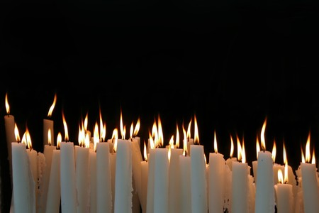 burning love: White Candle flames on a black background Stock Photo