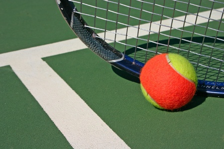 Yellow-red balls on a green tennis court photo