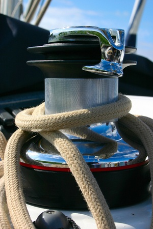 Winch on sailing boat with white cord photo