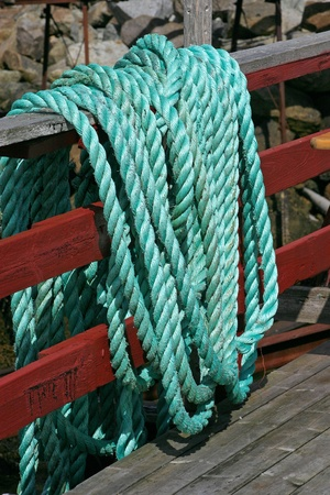 Green ship rope hanging on a fence photo
