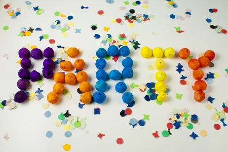 Party word written with small balls on background of confetti