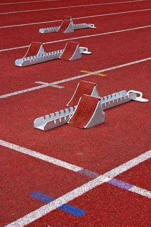 陸上競技の開始ブロックと、スタディオンで赤いランニング トラック