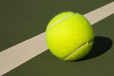 New yellow tennis balls on a green court