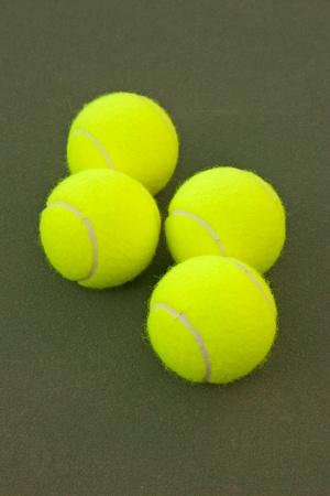 New yellow tennis balls on a green court photo