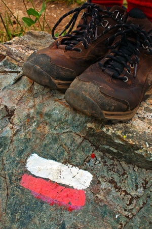 walking boots: Red White Hiking Trail Sign with Walking Boots Stock Photo