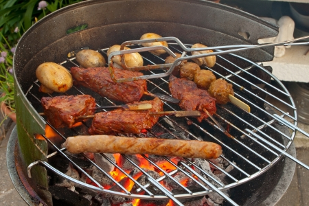 Cooking Meat and Vegetables on a Barbecue outside in the garden Imagens