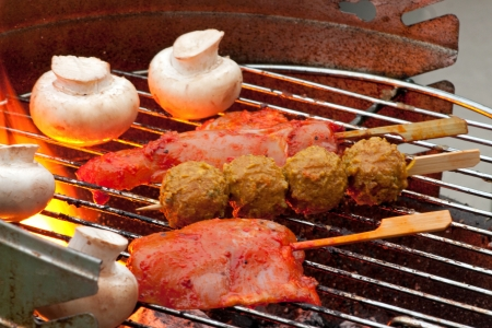 Cooking Meat and Vegetables on a Barbecue outside in the garden photo