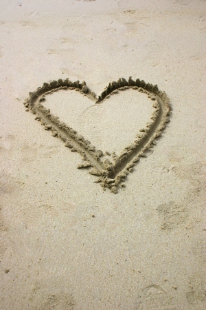 Heart written by hand in sand on the beach photo