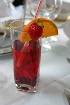 Red cocktail with orange and strawberry photo