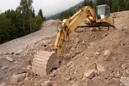 A yellow digger or excavator used to prepare a new track in the mountains photo
