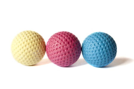 Yellow, Red and Blue colored Mini Golf balls on an isolated background photo