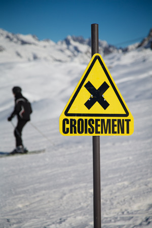 A skier passing by a sign of crossing slopes photo