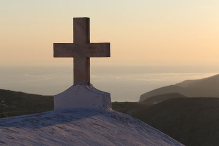 chora: Sunset and the cross of the church at the top of the hill in Chora, Folegandros