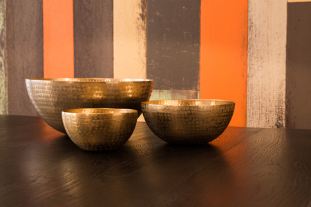 Three empty decorated metal bowls on a table