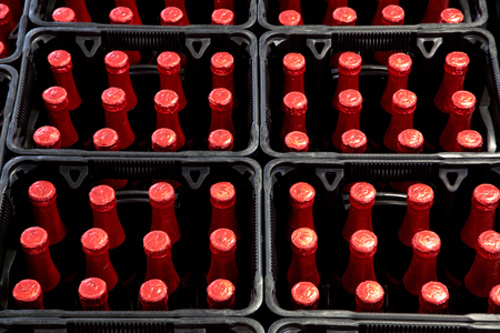 A group of red bottles in beer crates