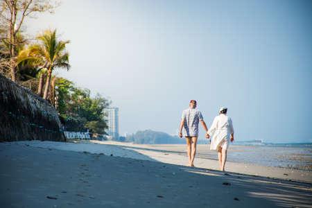 natue: Couples walking along  the beach.