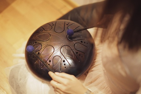 spirituality therapy: woman is playing on the steel tongue drum on the floor