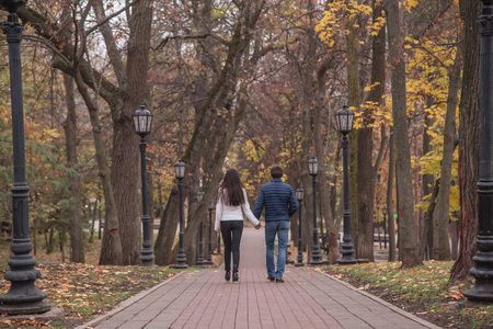 young man and woman are walking outside in a park