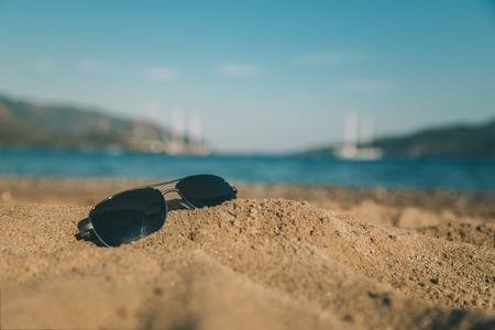bathe: Sunglasses on the beach Stock Photo