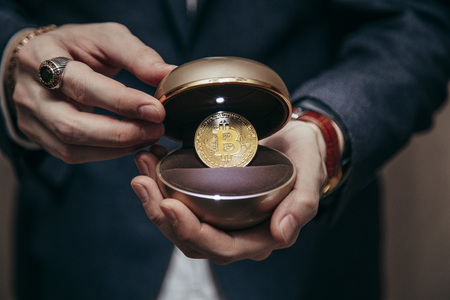 a man holds an enlarged box with bitcoin