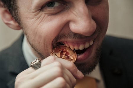 man is trying to break the bitcoin with his teeth