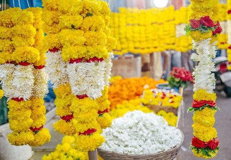 woman chooses a wreath of flowers in the market at India