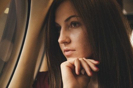 beautiful young woman sits in a plane near the window