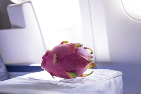 Fresh pink dragon fruit on the table in the plane for dinner during flight to tropic country