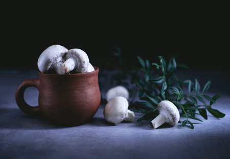 Champignon mushrooms in an old clay pot on a table in a dark Stock Photo