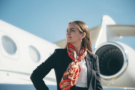 Bella giovane donna d'affari vicino al jet dell'aeroplano in una giornata di sole in aeroporto Archivio Fotografico