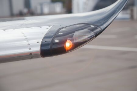Navigation light on the wing of jet airplane in airport