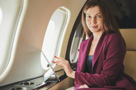 Young woman sits in a plane near the window 免版税图像
